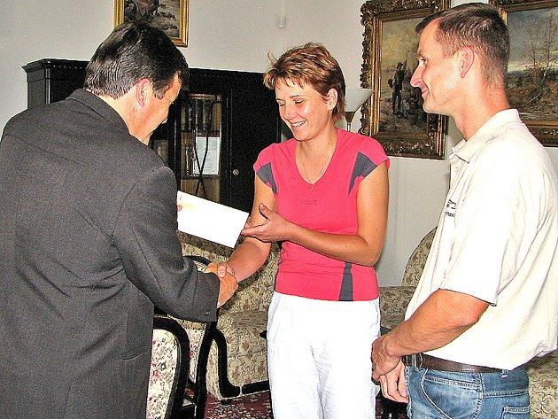Náměstek primátora Jan Smutný předává finanční dar šťastným rodičům.