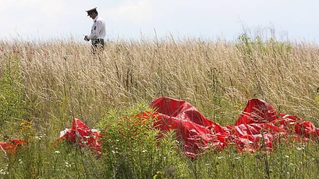 Část padáku leží poblíž místa, kam parašutisté dopadli.