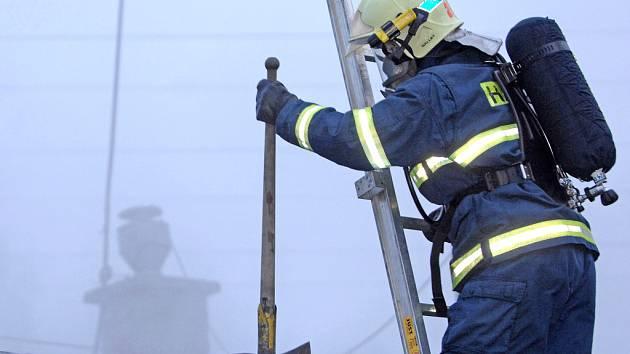 Hasič obhlíží střechu hořící budovy.