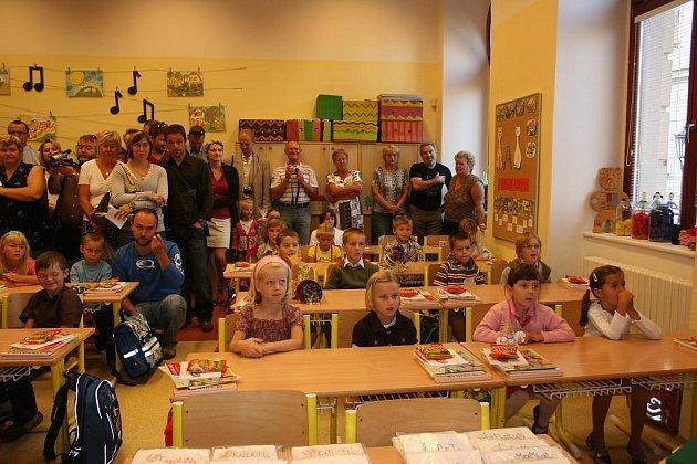 Děti v první třídě již sedí v lavicích a pozorně poslouchají svou učitelku