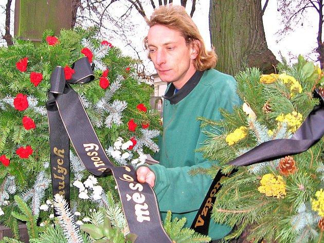 Hrobník Vratislav Bernard při instalaci věnců od kosmonoských spolků.