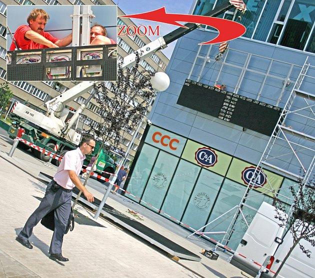 Pracovníci specializované firmy připevňují na stěnu Bondy centra v Mladé Boleslavi první místní velkoplošnou obrazovku. Ta bude po vzoru pražkých obchodních domů sloužit k reklamě.