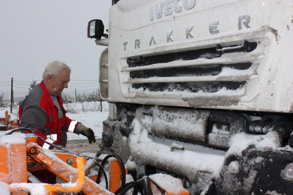 """Řidič posypového vozu Pavel Prodl čistí svůj """"stroj""""."""