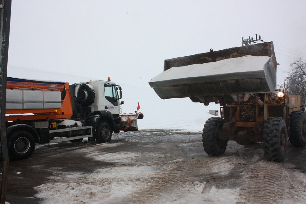 Řidiči posypových vozů si sůl naloží sami pomocí bagru.