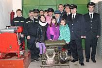 DOBROVOLNÍ hasiči ze Suhrovic pózují v hasičské zbrojnici u techniky.
