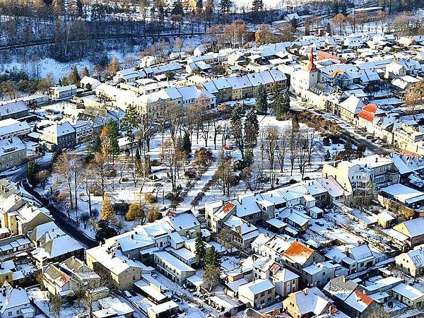 BĚLÁ POD BEZDĚZEM. Náměstí města pod Bezdězem je plné vzrostlých jehličnanů a opadaných listnáčů.