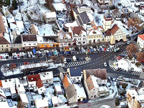 DOBROVICE. Pohled na náměstí města Dobrovice sradnicí.