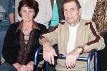 Starosta Kosmonos Vladimír Dlouhý s chodítkem, které mu pomohá při pohybu. Vlevo sedí místostarostka Zdeňka Procházková.
