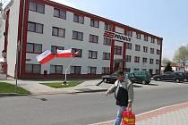 Před ubytovnou s polskými dělníky vlají vlajky a hoří svíčky.