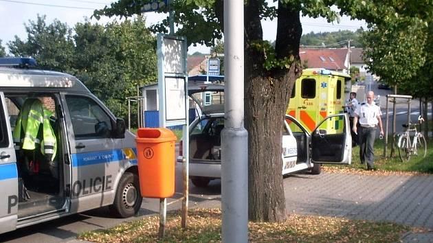 Sanitka už je pryč, Policie ČR přebírá místo, vpravo je vidět opřené kolo, o které se postarali strážníci.
