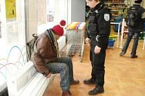 Podřimující bezdomovec u pokladny.