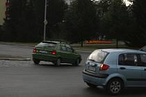 Hráškově zelená felicie jede tak zběsile, že přejíždí přes dlažební kostky kruhového objezdu.