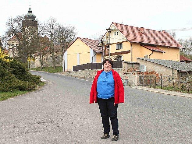 JANA SVOBODOVÁ, starostka Skalska, uprostřed obce. Nad ní se ukazuje historický kostel se zvonicí.