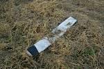 Zničený patník, který leží v příkopě.