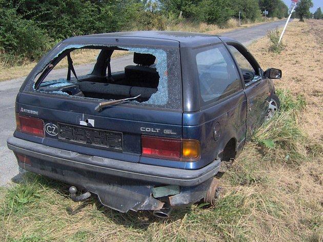 Rozbité a rozkradé auto stojí mimo silnici na křižovatce z Katusic na Kováň.