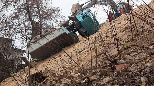 Náklaďák spadl pod sklárnou ze stráně a kameny ohrožují děti i dospělé