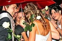 MATURANTY zasypali návštěvníci plesu drobnými mincemi, před kterými se studenti kryli deštníky.