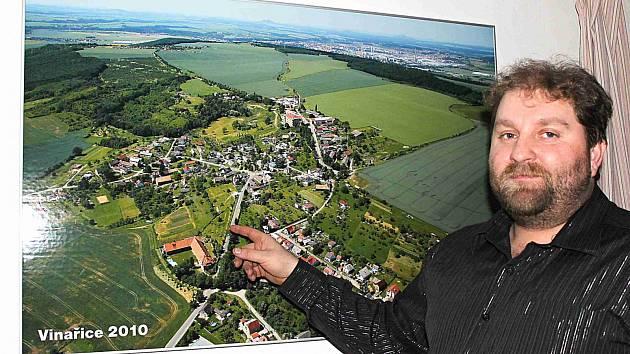 STAROSTA Jiří Kohout ukazuje fotografii obce. Novou pořídí, až se ve Vinařicích dostaví rodinné domy.