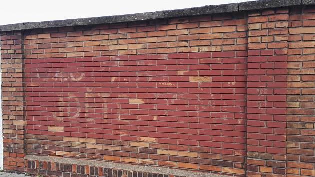 """Na zdi u škodovácké třetí brány lze rozluštit další nápis – """"OKUPANTI JDĚTE DOMŮ""""."""