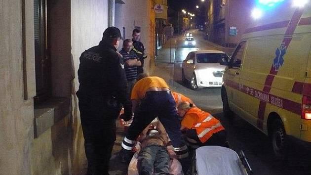Záchranáři se strážníky ošetřují pobodané muže v Mladé Boleslavi.