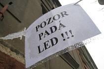 Padající sníh a led ze střech domů ohrožuje obyvatele města.