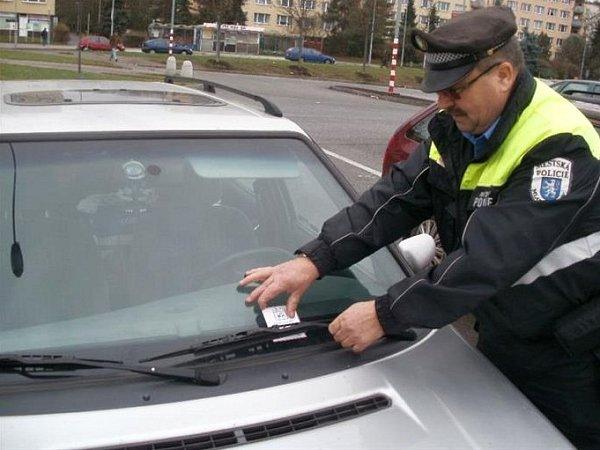 STRÁŽNÍK za stěrač vozidla umisťuje upozornění, že auto není trezor. Cennosti ve vozech lákají zloděje.