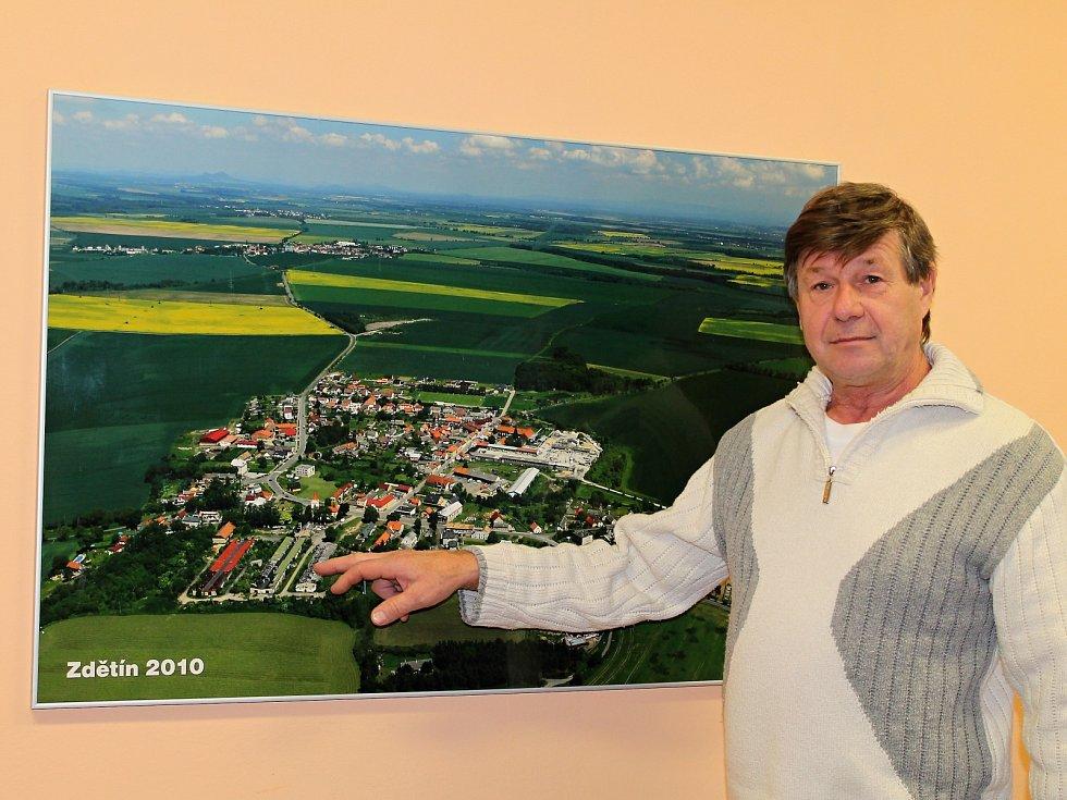 Starosta František Němeček na letecké fotografie ukazuje, kde stály nevzhledné kravíny a kde dnes vyrůstají rodinné domy.