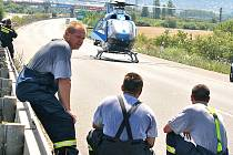 Hasiči pozorují odlet vrtulníku od jedné z nehod.