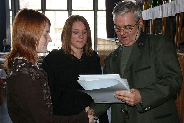 Předseda MO ČRS Jan Bačina předává mladým rybářkám odznaky odbornosti.