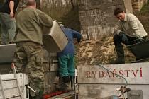 PŘED samotným nasazováním ryb do Strenického potoka museli rybáři na 150 kilogramů pstruhů přeložit z nákladního auto na svůj vůz.
