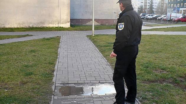 Strážníci dokumentují propadlý chodník.