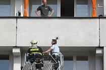 Hasiči, záchranáři a policisté při zásahu u páru, který v pátek dopoledne vyhrožoval skokem z okna na náměstí Míru v Mladé Boleslavi.