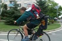 Žena s dítětem na zádech ujížděla po rušné ulici
