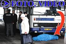 Cestující na autobusovém stanovišti míjí tělo mrtvého řidiče ležící pod modrou plachtou.