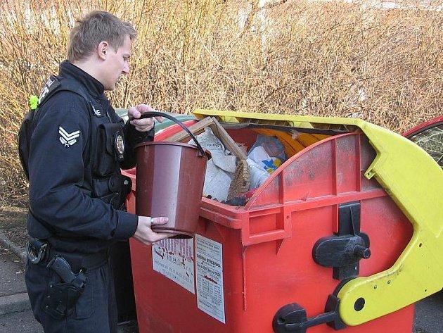 Strážník městské policie uhasil požár kbelíkem vody.