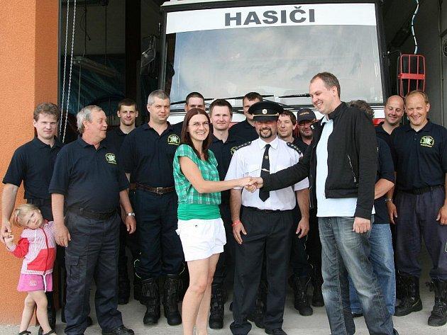 Hasiči z Kněžmosta před hasičskou zbrojnicí s Jitkou Bartošovou a Robinem Povšíkem.