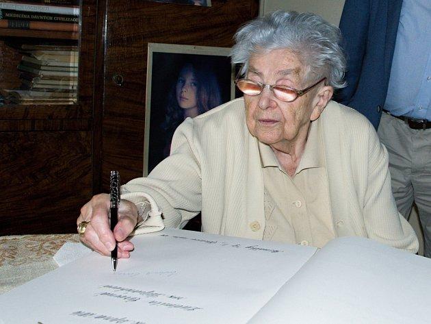 Ludmila Novotná se podepisuje do pamětní knihy města.