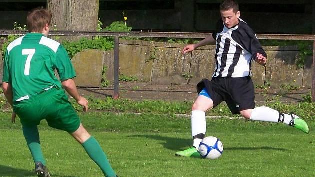 Mnichovohradišťský hráč Jiří Sameš (vpravo) se chystá centrovat přes bránícího hráče Zásmuk Miroslava Černého.