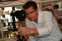 Miloš Adámek se svým fotoaparátem při práci v jedné z prodejen na Staroměstském náměstí v Mladé Boleslavi.