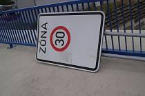 """Dopravní značka """"ZÓNA 30"""", kterou kdosi opřel o zábradlí."""
