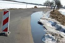 Voda z polí pomalu zaplavuje silnice.