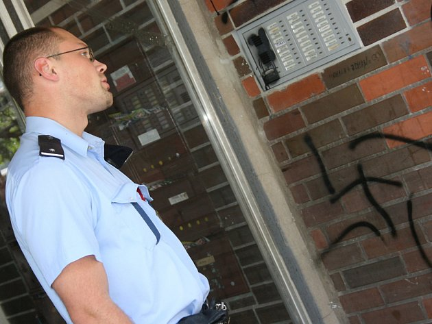 Policisté zajišťují stopy v domě počmáraném nacistickými symboly a hovoří s místními lidmi.