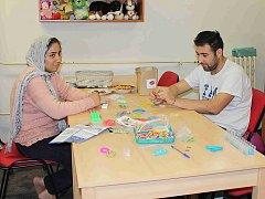 Uprchlíci tráví volný čas volnočasovými programy. Na snímku jsou v knihovně.