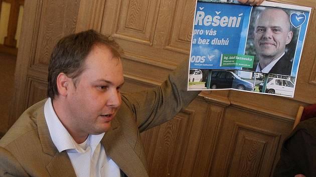 Zastupitel Robin Povšík s billboardem Adolfa Beznosky, kde hlásá budoucnost bez dluhů.