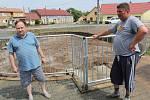 Přívaly vody a bahna z polí zaplavily Slavětice. V nové požární nádrži na návsi je teď místo dvou metrů vody dva metry bláta. Vpravo starosta René Moravec.