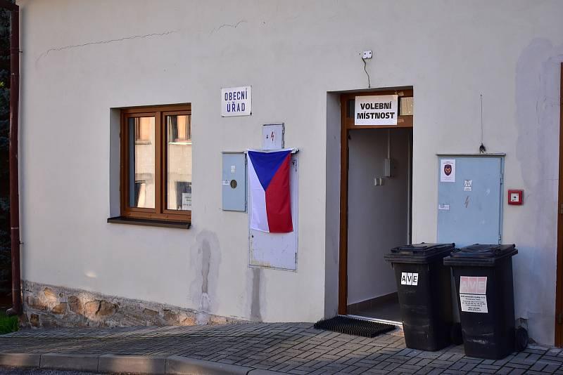 Vlajka na volební místnosti nevisí na žerdi, nýbrž je připevněna karabinkami na elektrorozvodné desce.