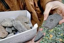 Archeolog Vokáč drží v rukou kamennou sekerku. Dobře je vidět nedovrtaný otvor. Kámen se pravděpodobně rozlomil člověku dřív, než stačil dílo dokončit.