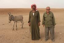 Náhodní kolemjdoucí procházející vesnicí. V typickém oděvu a typické krajině. Tell Arbid.