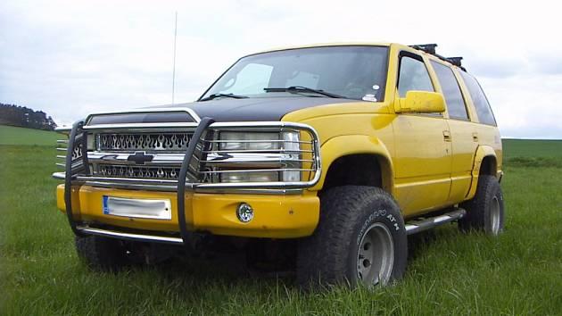 Jasně žlutý Chevrolet Tahoe Z71 ročníku 1999 s pohonem všech čtyř kol. Na první pohled zaujme leštěná mřížka chladiče se symboly plamenů.