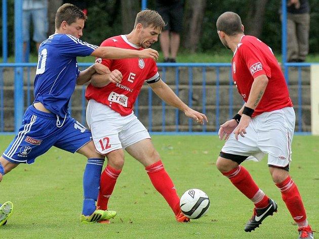 Třebíčské fotbalisty (v červeném u míče kapitán David Komínek) zítra čeká domácí zápas proti Zábřehu.